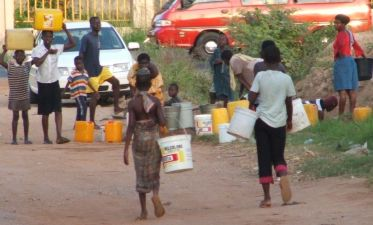 Children fetching water from a broken pipe