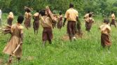 Carrying stakes to mark out for tree planting on school grounds